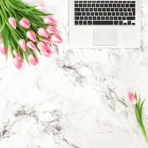 Office desk flat lay with flowers. Laptop and tulips on marble stone background
